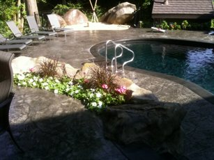 stamped concrete pool deck with garden and lounge area