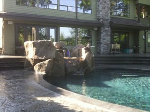 stamped concrete patio with rock waterfall