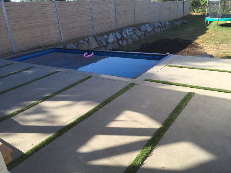 close up of grass strips in concrete pool deck