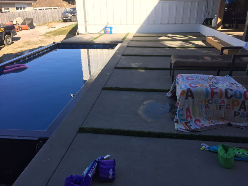 concrete pool deck with grass strips between slabs