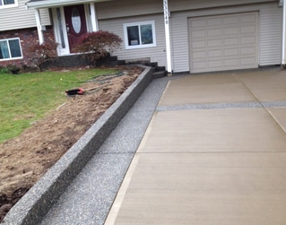 colored concrete driveway with exposed aggregate border