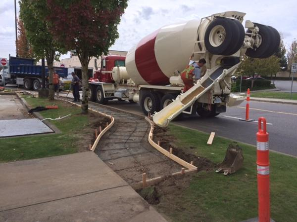 Pouring a curved sidewalk in the parking lot of a commercial shopping mall.